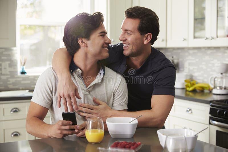 Couples gais masculins dans leur 20s embrassant dans leur cuisine image libre de droits