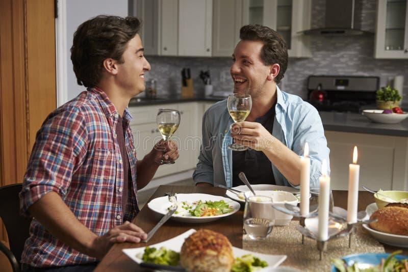 Couples gais masculins faisant un pain grillé au dîner dans leur cuisine photo stock
