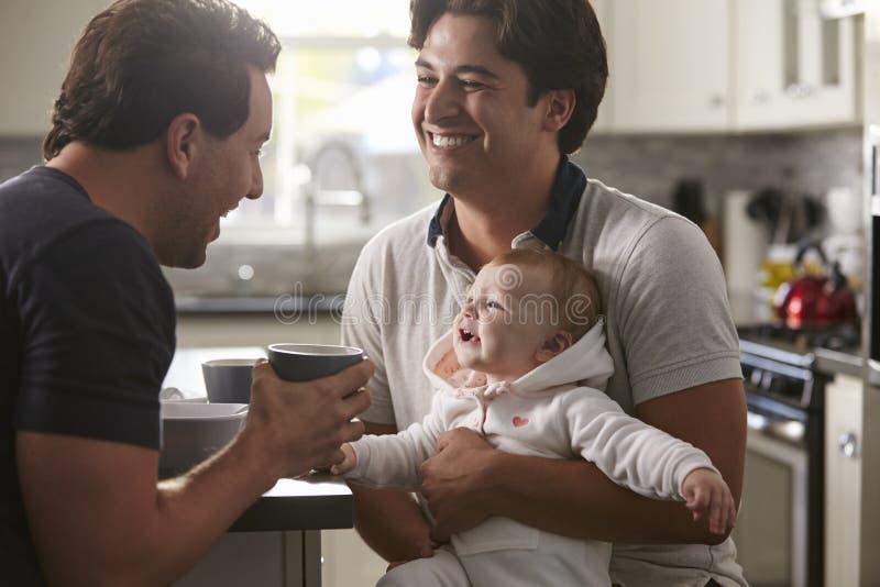 Couples gais masculins tenant le bébé dans leur cuisine image libre de droits