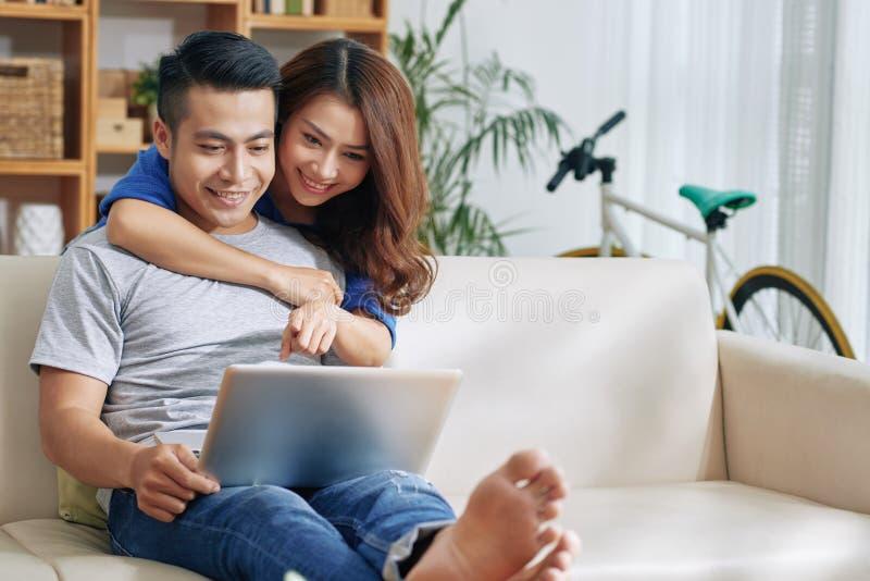 Couples gais utilisant l'ordinateur portable sur le divan photos libres de droits