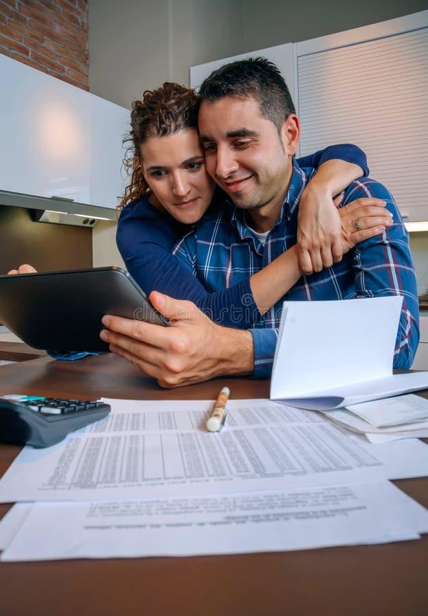 Couples gais utilisant le comprimé numérique à la maison de cuisine photo libre de droits