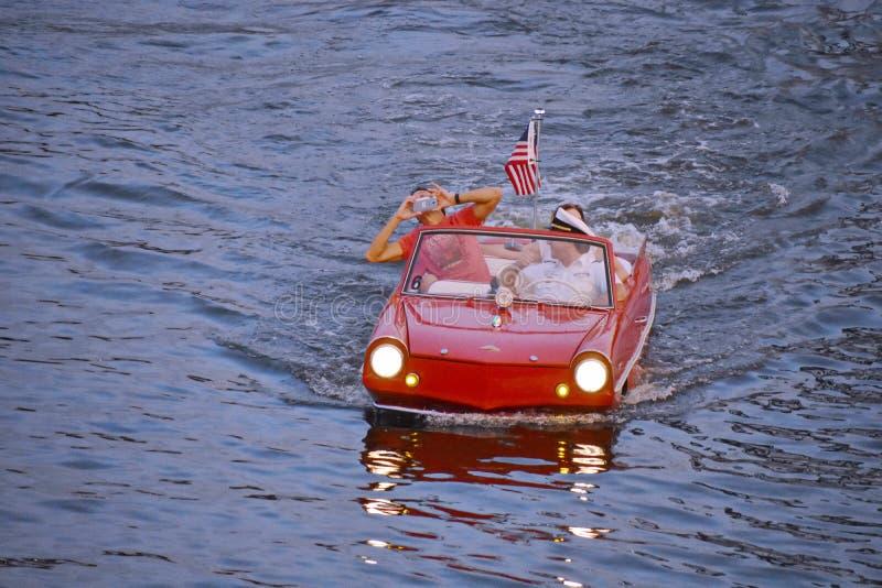 Couples gentils appréciant le tour rouge amphibie de voiture au-dessus du lac bleu à la région de Buena Vista de lac images stock