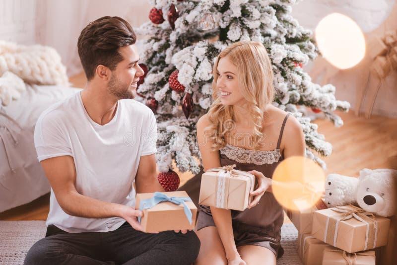 Couples gentils beaux échangeant leurs cadeaux de Noël image stock