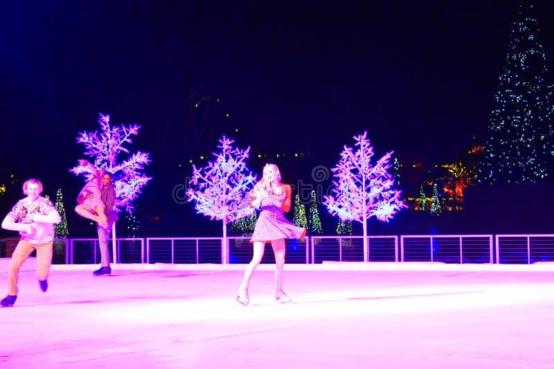 Couples gentils patinant sur la glace à l'exposition de Noël dans la région internationale d'entraînement photographie stock