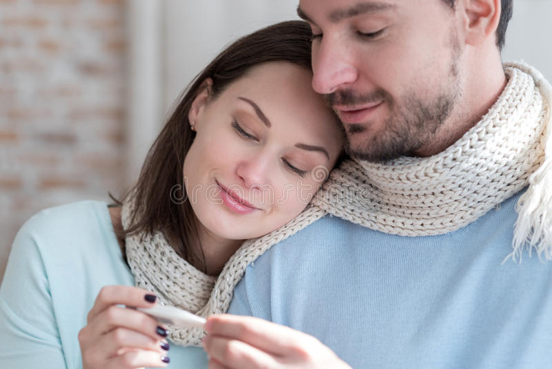 Couples gentils positifs tenant un thermomètre de corps photographie stock libre de droits