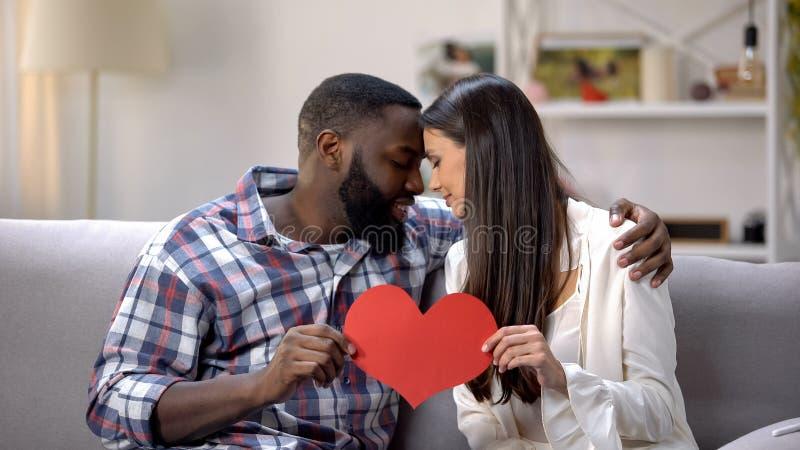 Couples gentils touchant des fronts et montrant le coeur de papier à la caméra, tendresse photographie stock libre de droits