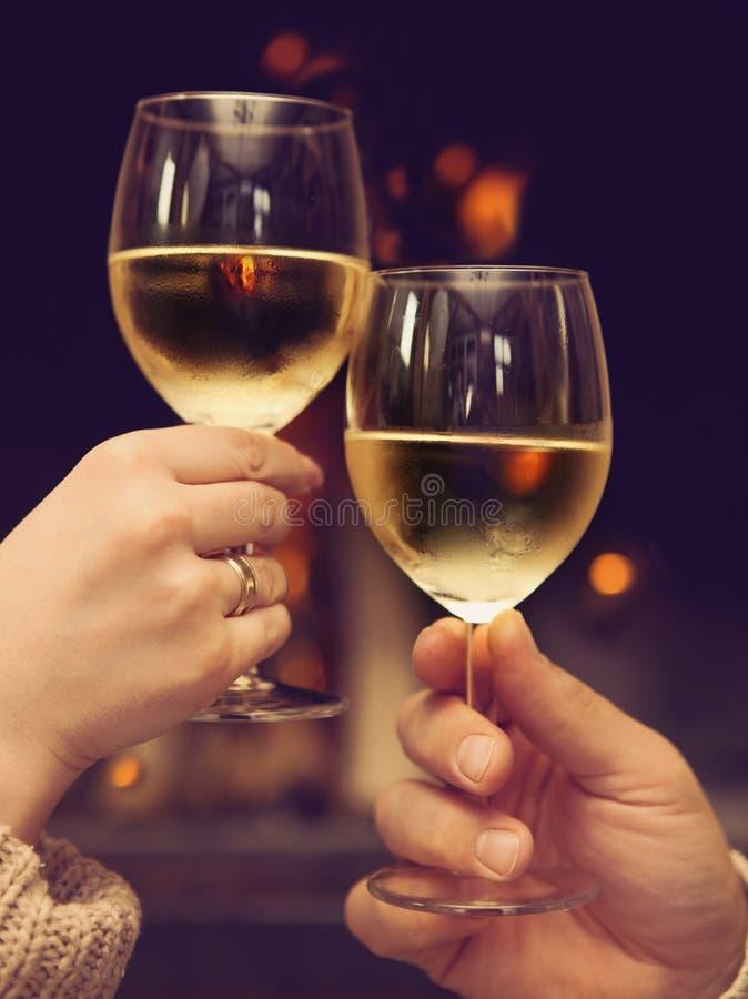 Couples grillant des verres à vin devant la cheminée allumée photographie stock