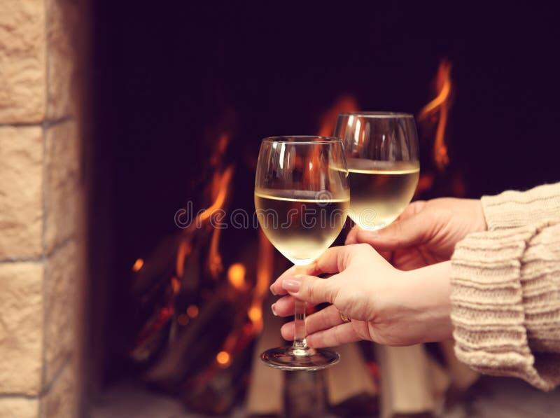 Couples grillant des verres à vin devant la cheminée allumée photographie stock libre de droits