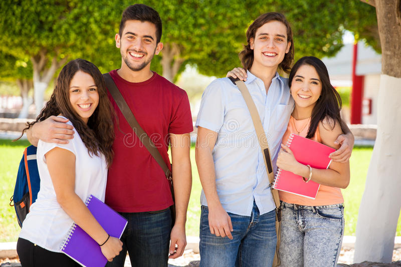 Couples hanging out at school. Portrait of two Hispanic couples hanging out together at a university and smiling stock photography