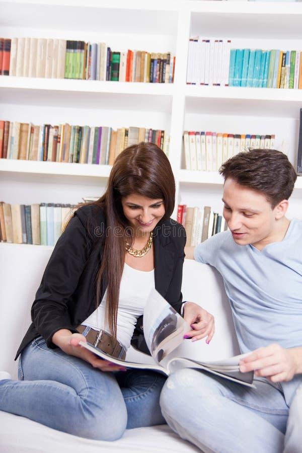 Couples heureux à la maison lisant des journaux devant la bibliothèque images libres de droits