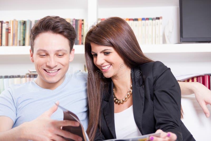 Couples heureux à la maison lisant le magazine photo stock