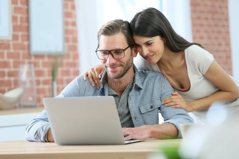 Couples heureux à la maison utilisant l'ordinateur portable photo stock