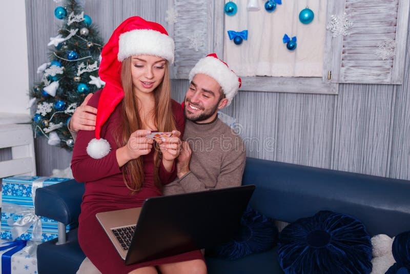 Couples heureux, à la veille de la nouvelle année, faisant des achats en ligne, une fille regardant une carte de crédit photo stock