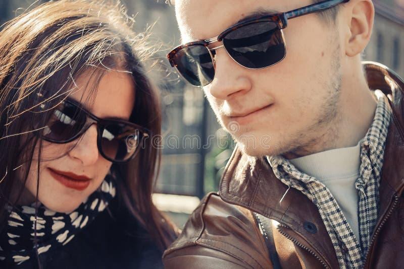 Couples heureux élégants dans des lunettes de soleil souriant et ayant l'amusement en soleil photos stock