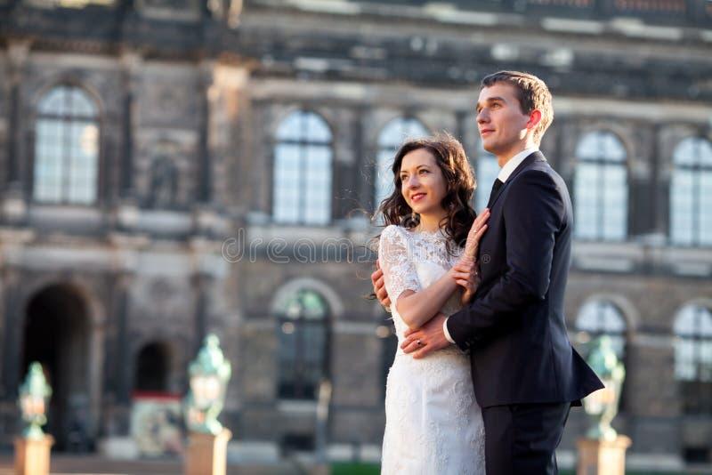 Couples heureux élégants de mariage sur château de la belle Renaissance de fond le vieux Marié et jeune mariée romantiques de nou images stock