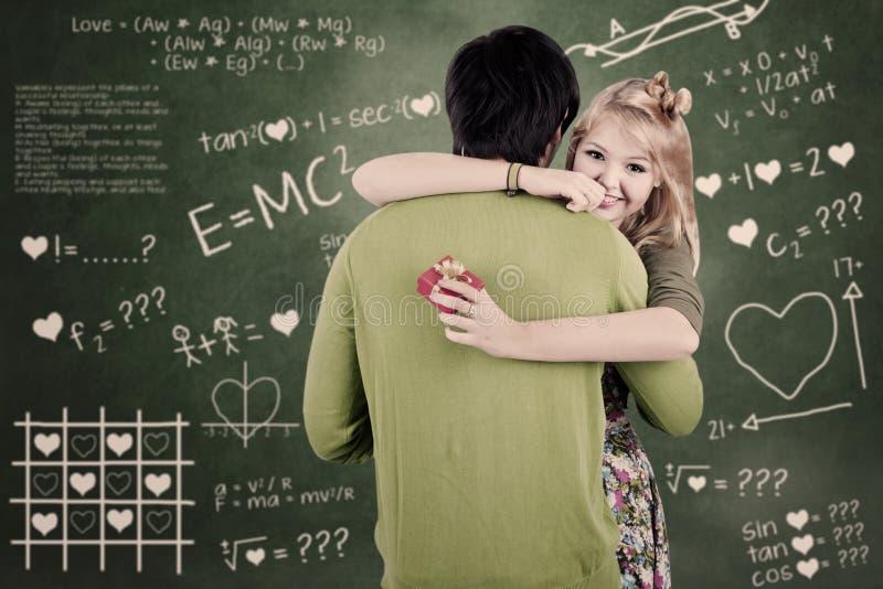 Couples heureux étreignant dans la classe photos stock