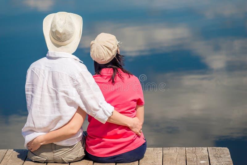 Couples heureux étreignant et appréciant le repos près du beau lac, vue photographie stock libre de droits