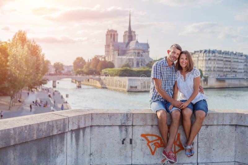 Couples heureux ?treignant pr?s de la cath?drale de Notre-Dame ? Paris Touristes appr?ciant leurs vacances dans les Frances Date  photo libre de droits