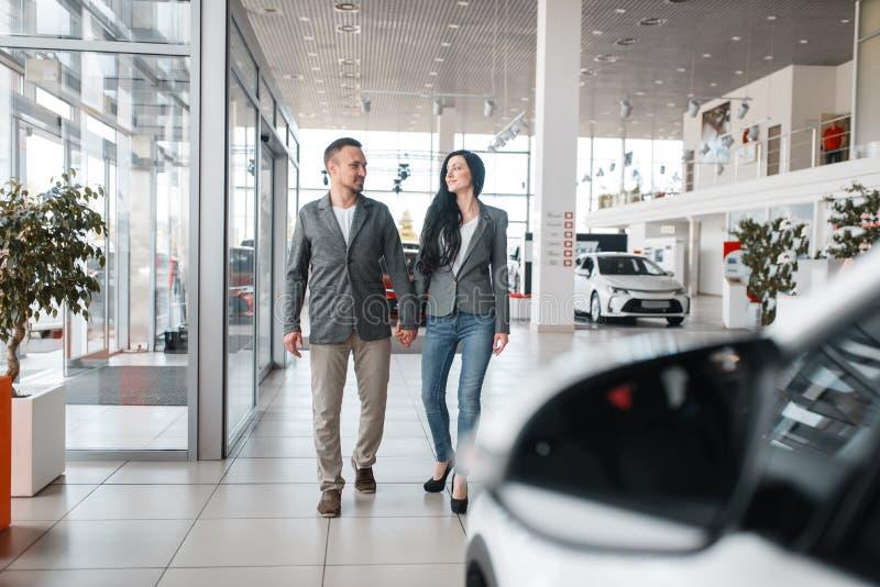 Couples heureux achetant la nouvelle voiture dans la salle d'exposition photographie stock libre de droits