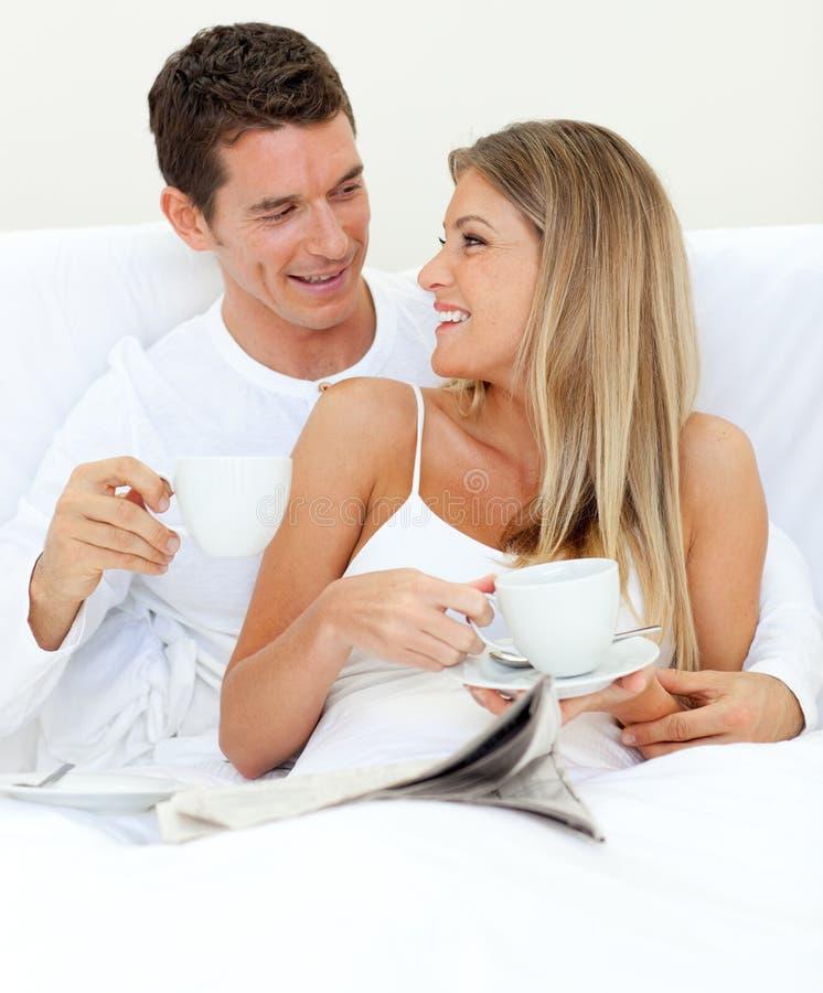 Couples heureux affichant un journal photographie stock libre de droits