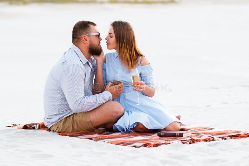 Couples heureux appréciant le pique-nique sur la plage blanche de sable et buvant de vin ou du champagne pendant le dîner romanti images libres de droits