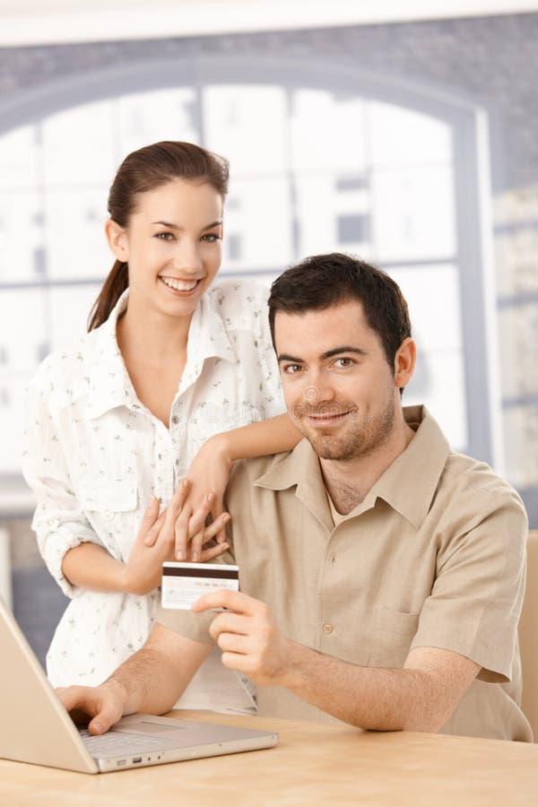 Couples heureux appréciant le sourire en ligne d'achats image stock