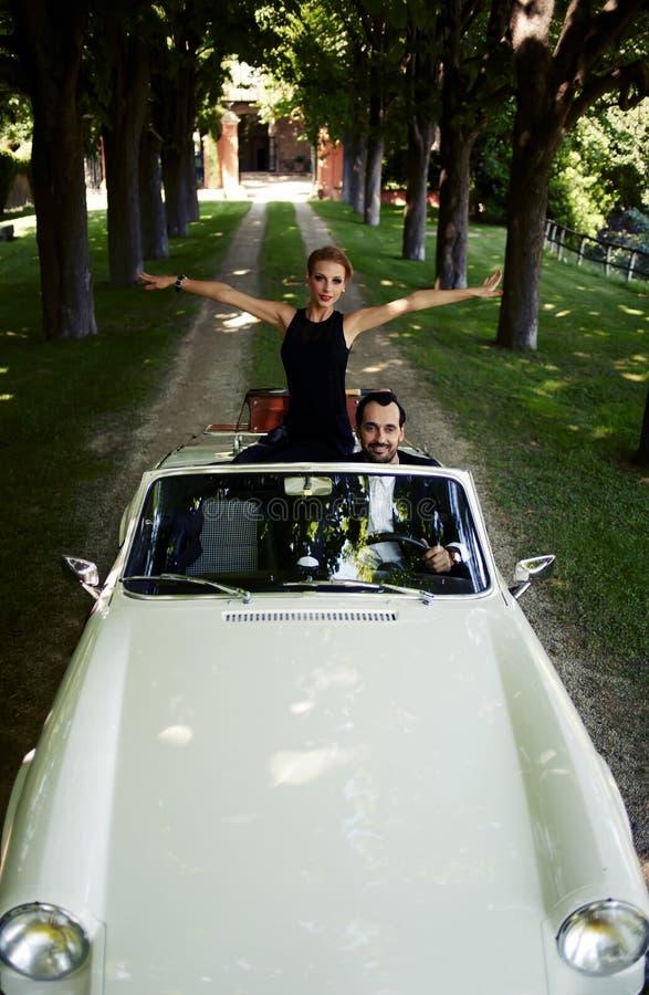 Couples heureux appréciant un tour sur leur voiture convertible de luxe pendant l'été photos stock
