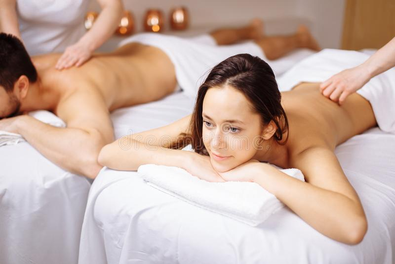 Couples heureux atteignant le massage la station thermale image libre de droits