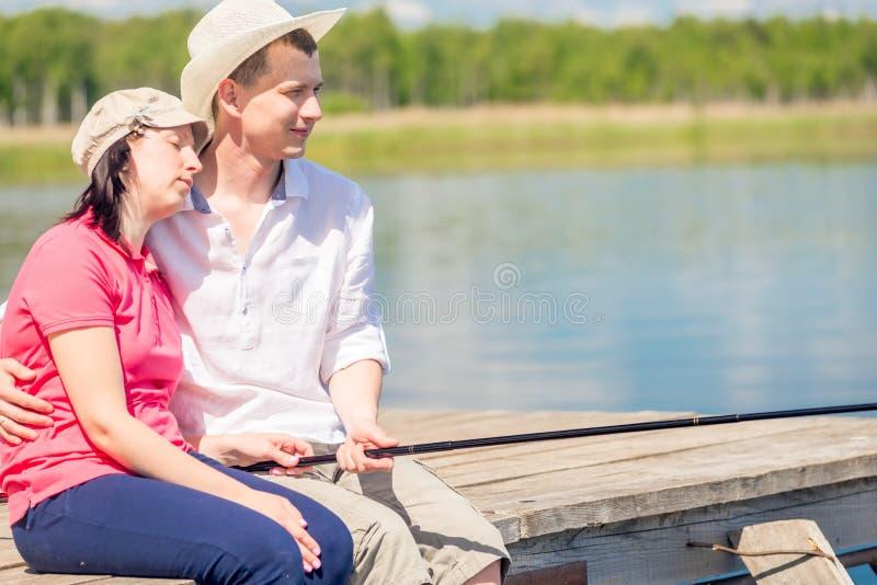 Couples heureux aux pieds nus sur le pilier pour pêcher un poisson images libres de droits