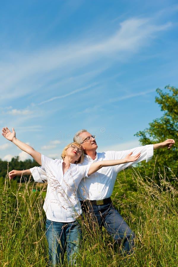 Couples heureux ayant l'amusement à l'extérieur en été images stock