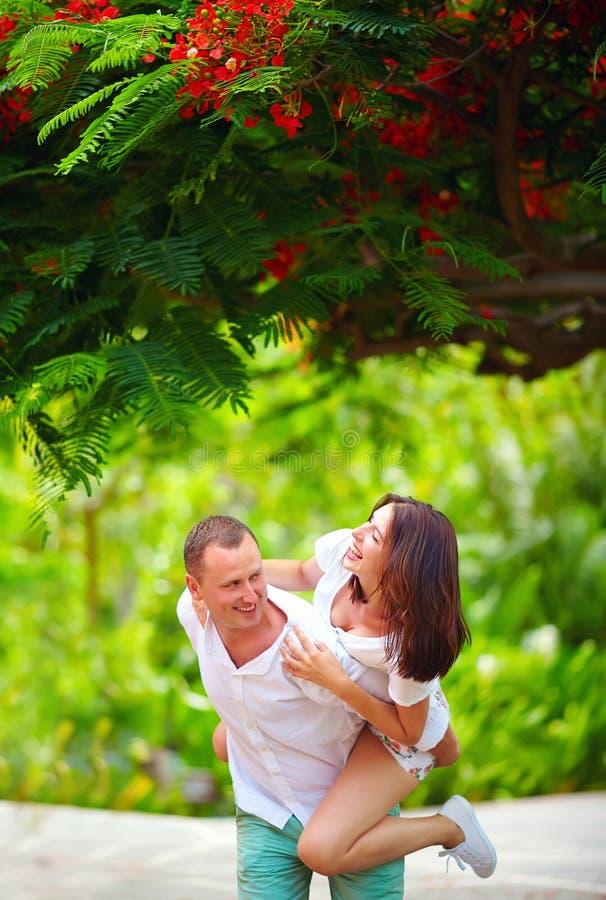 Couples heureux ayant l'amusement dans le parc de floraison photo stock