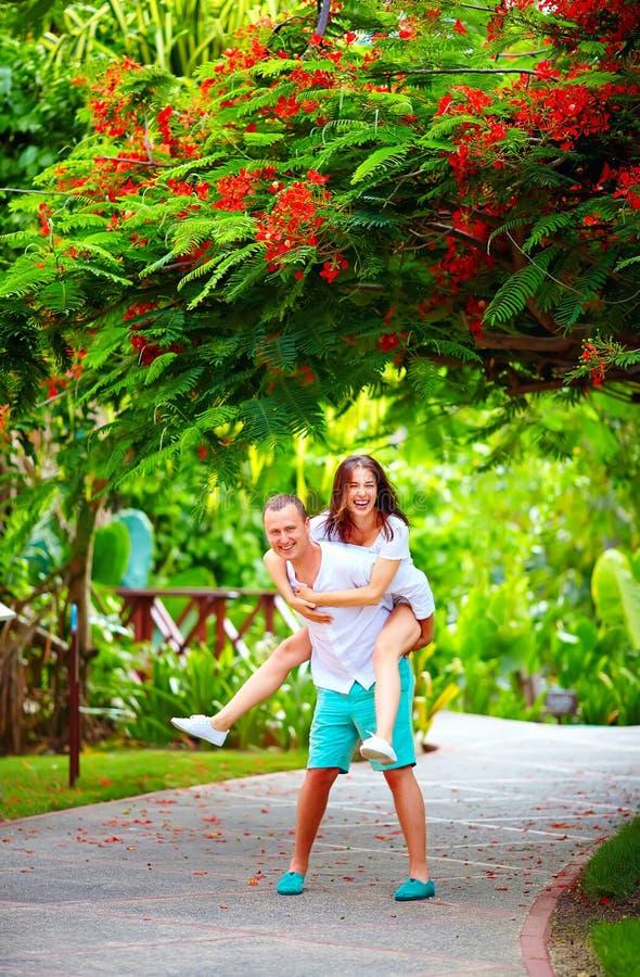 Couples heureux ayant l'amusement dans le parc de floraison photos libres de droits