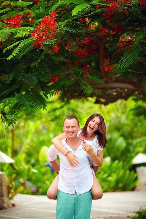 Couples heureux ayant l'amusement dans le parc de floraison images stock