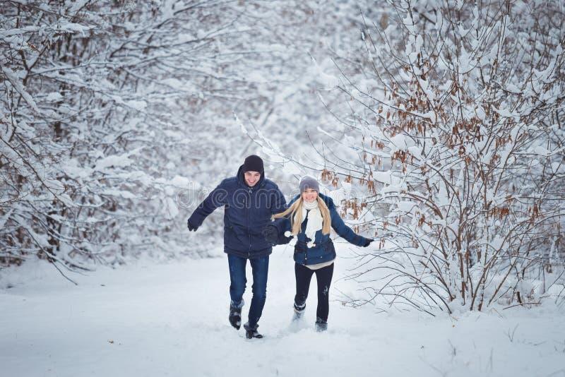 Couples heureux ayant l'amusement dehors dans le parc de neige Vacances de l'hiver images stock