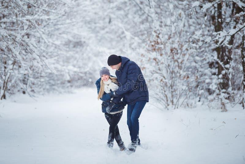 Couples heureux ayant l'amusement dehors dans le parc de neige Vacances de l'hiver images libres de droits