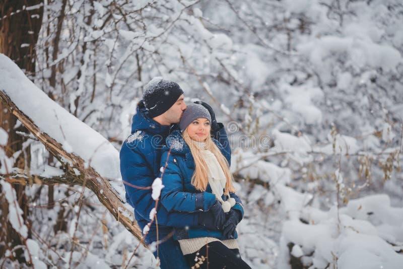 Couples heureux ayant l'amusement et l'embrassant dehors dans le parc de neige Vacances de l'hiver photo libre de droits