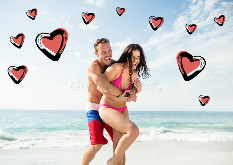 Couples heureux ayant l'amusement sur la plage image libre de droits