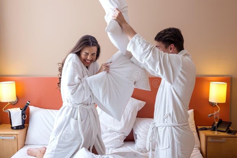 Couples heureux ayant le combat d'oreiller dans la chambre d'hôtel photo stock