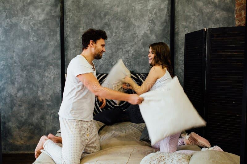 Couples heureux ayant le combat d'oreiller dans le lit à la maison photos stock