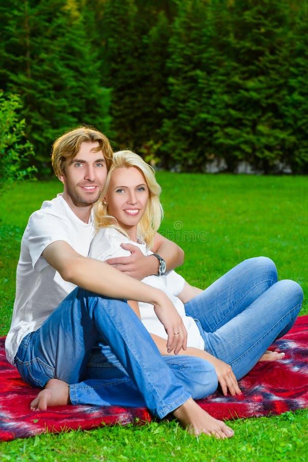 Couples heureux ayant le pique-nique extérieur un jour d'été photo libre de droits