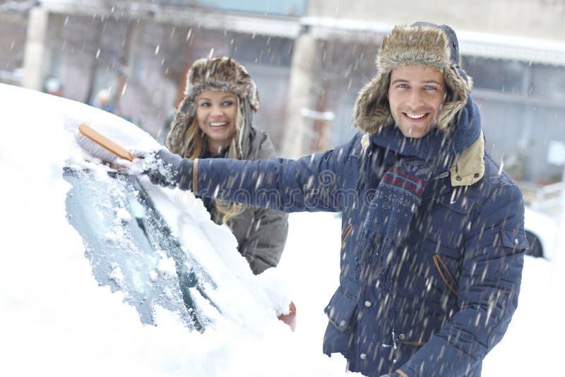 Couples heureux balayant la neige de la voiture images stock