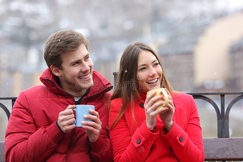 Couples heureux buvant les boissons chaudes regardant le côté en hiver photos stock