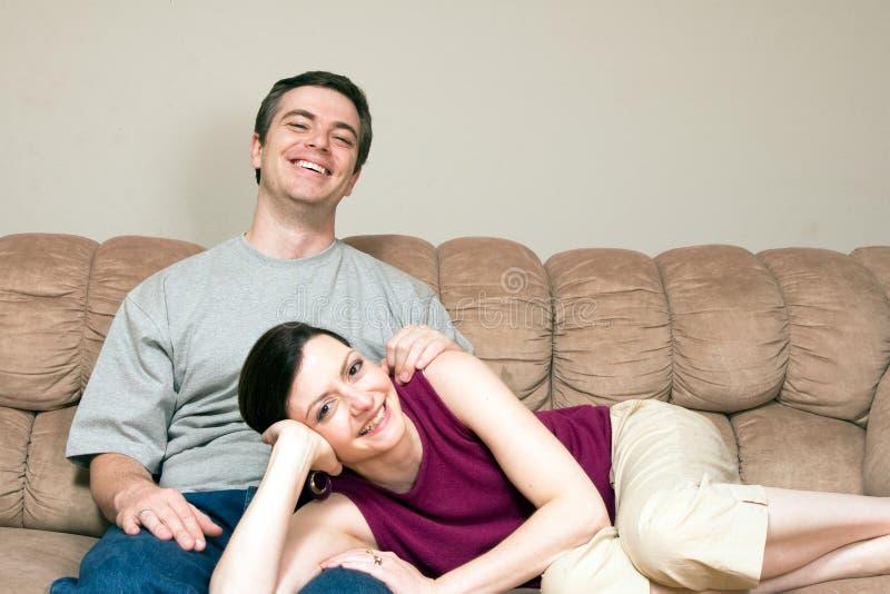 Couples heureux caressant sur un divan - horizontal image stock