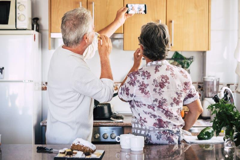 Couples heureux caucasiens adultes supérieurs à la maison dans la cuisine faisant cuire et collaborant avec la joie et le bonheur photographie stock libre de droits