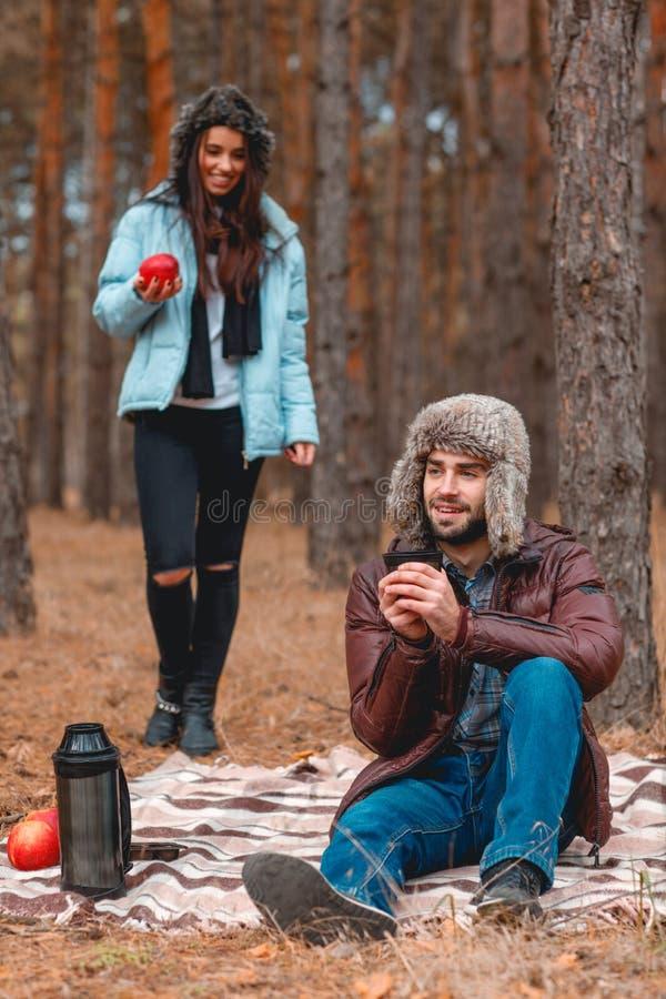 Couples heureux, chaudement habillés, ayant l'amusement dans la forêt froide d'automne photos libres de droits