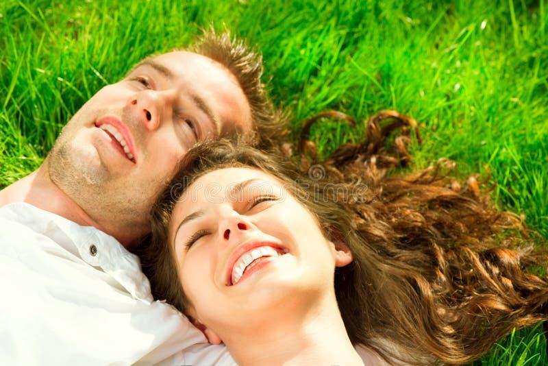 Couples heureux détendant sur l'herbe verte photos libres de droits