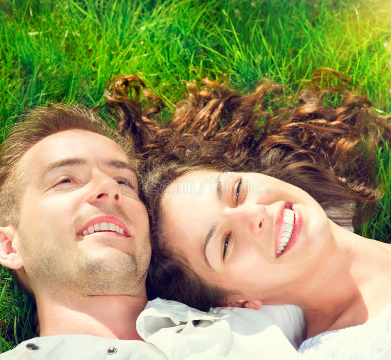 Couples heureux détendant sur l'herbe verte photos stock