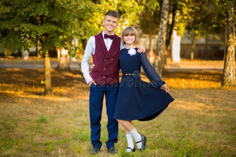 Couples heureux d'adolescent des étudiants de lycée dans l'uniforme scolaire de fête sur le parc d'automne de fond Début des leço image libre de droits