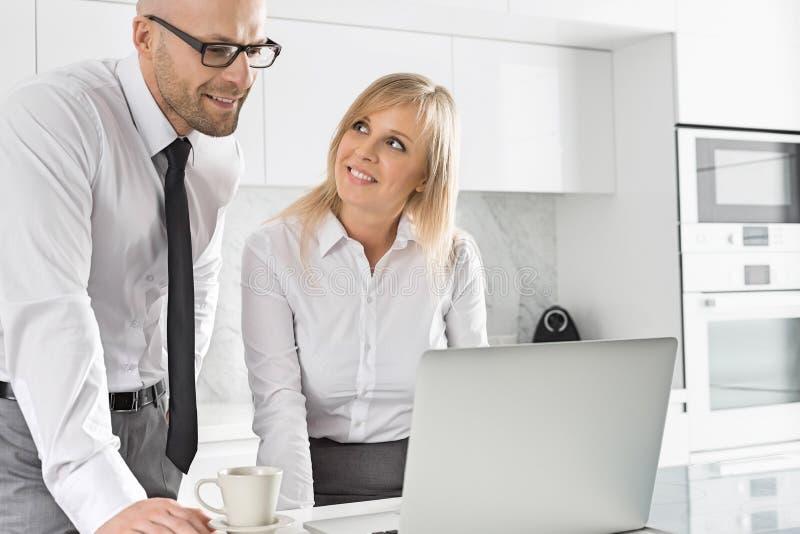 Couples heureux d'affaires travaillant sur l'ordinateur portable dans la cuisine image stock