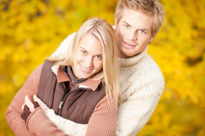 Couples heureux d'automne étreignant ensemble en stationnement images stock
